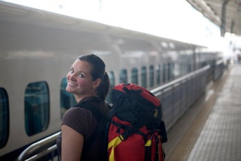 young woman wearing backpack at train