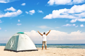 man on beach with tent