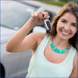 Happy young woman with keys to rental car