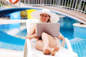 woman at pool with laptop