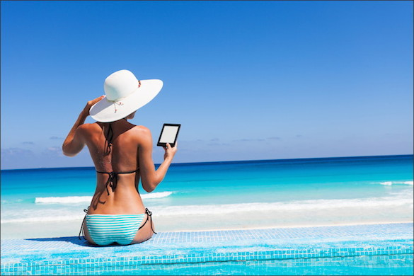 woman at edge of pool wearing a bikini and reading a kindle