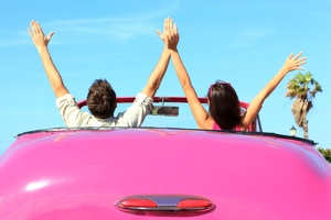 couple with hands in the air in pink convertable