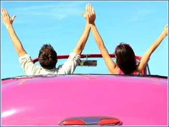 pink convertable and happy couple on road trip