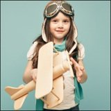 little girl holding wooden toy airplane