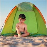 little boy on beach in green tent