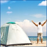 happy man on beach with tent