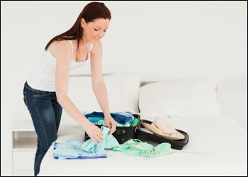 young woman packing carry on luggage