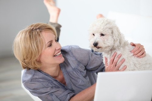 woman and dog on floor with laptop