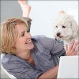 mature woman and dog on floor with laptop