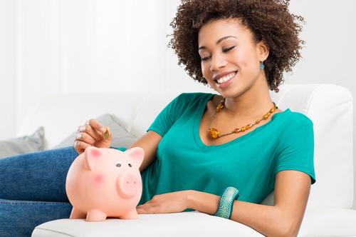 woman depositing a coin into a piggy bank