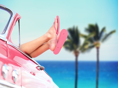 Woman with pink flip flops having fun in pink car