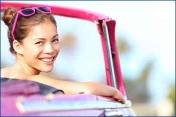 Smiling woman in vintage car