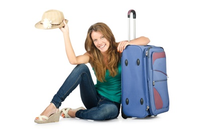 young woman sitting with blue suitcase